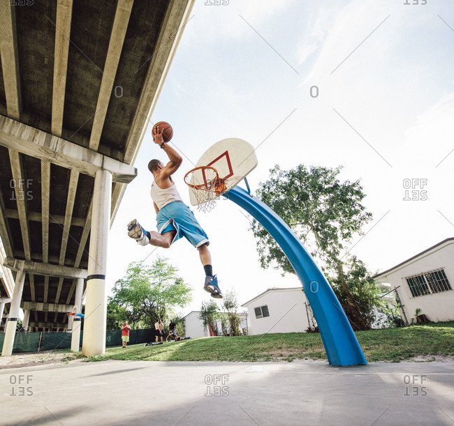 Low angle view of young man in mid air holding basketball jumping for hoop