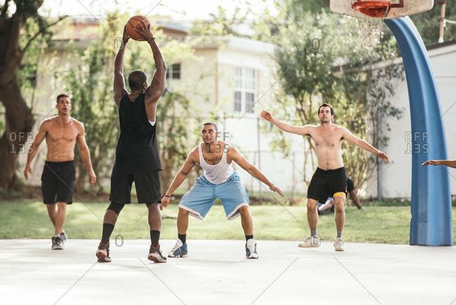 Men on basketball court playing basketball, defending hoop