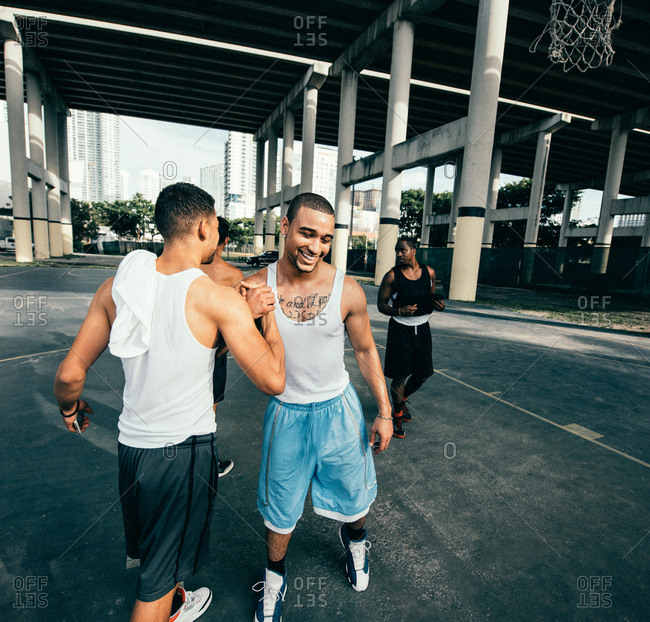 Young men on basketball court connecting with handshake after basketball game smiling