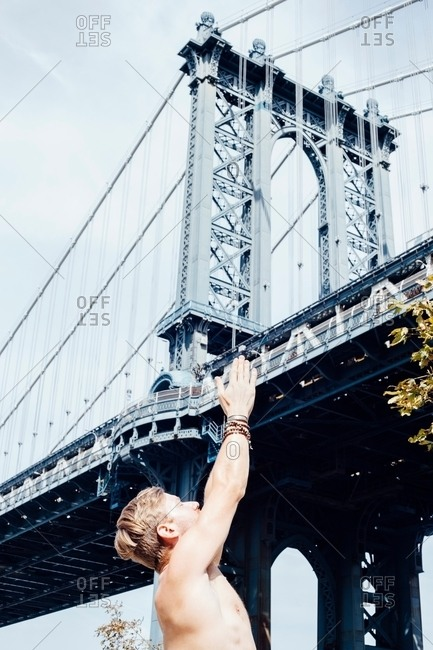 Man meditating with hands raised together in front of Manhattan Bridge, New York, USA