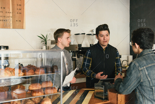 Manager explaining problem to customer at coffee shop counter
