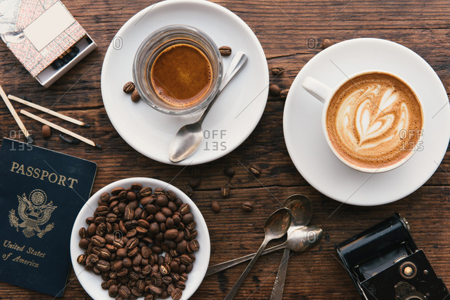 Overhead view of coffee's, coffee beans and American passport on coffee shop table