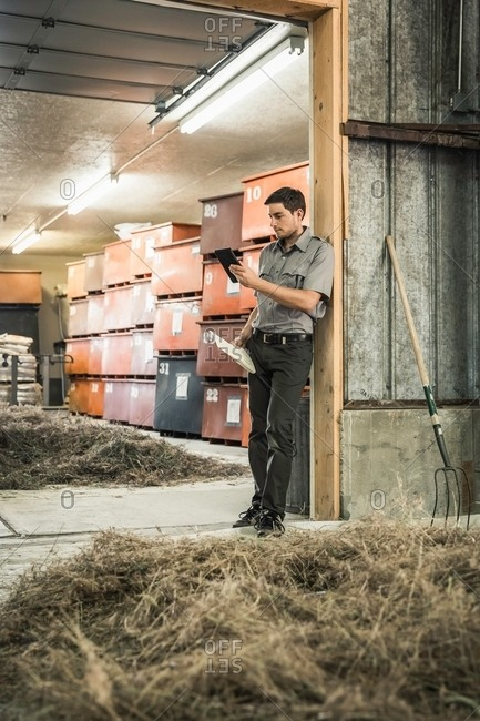 Scientist reading digital tablet in plant growth research centre barn