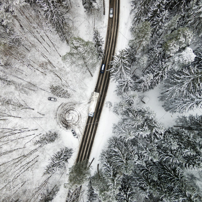 Cars on a snowy highway in a forest