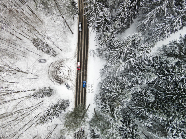 Cars traveling on a snowy highway in a forest