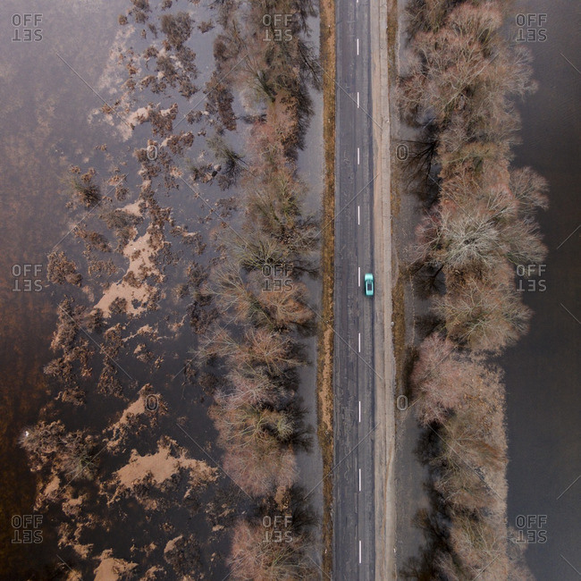 Car traveling on a road surrounded by floodwaters in Lithuania