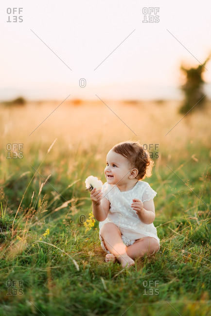 Smiling toddler sitting by herself in a meadow