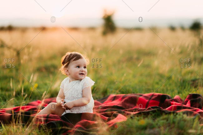 Toddler sitting by herself on a blanket in a field