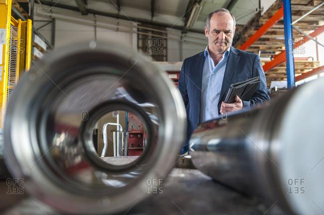 Senior man with digital tablet looking on hydraulic cylinder