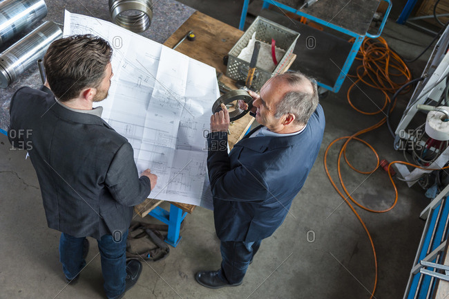Two engineers with construction plan talking, hydraulic cylinder