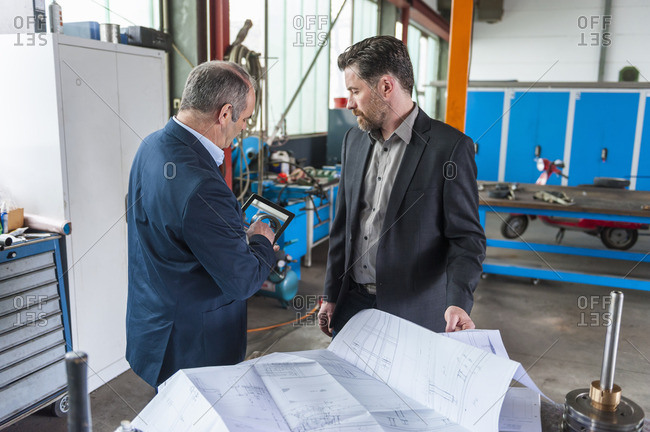 Two engineers with digital tablet, construction plan in front of hydraulic cylinder