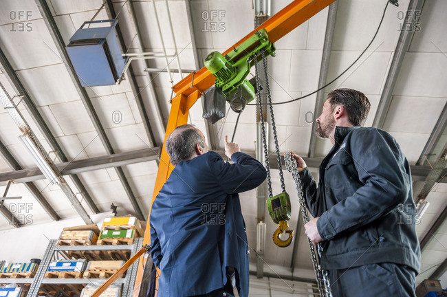Manager and worker in workshop, hoist
