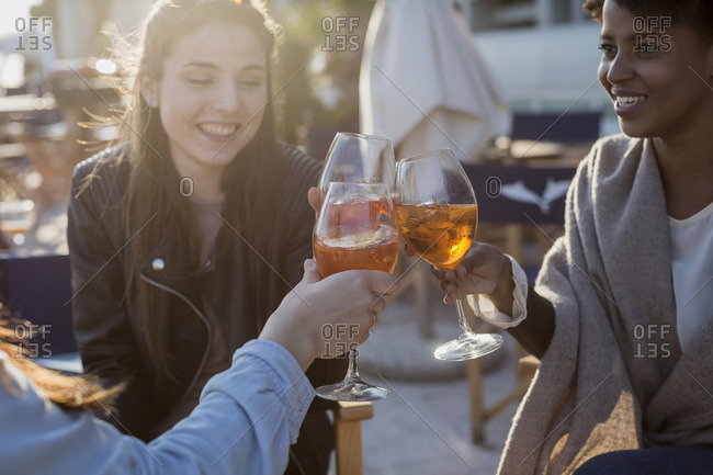 Young women sitting in bar drinking aperitif