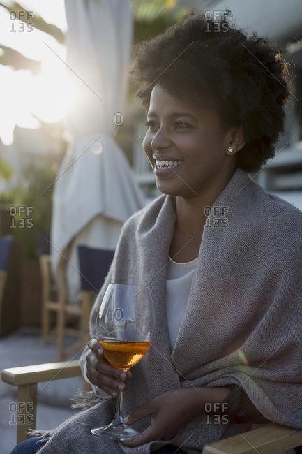 Young woman sitting in bar drinking aperitif