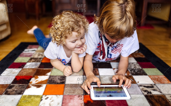 Two boys lying on the floor at home playing with digital tablet