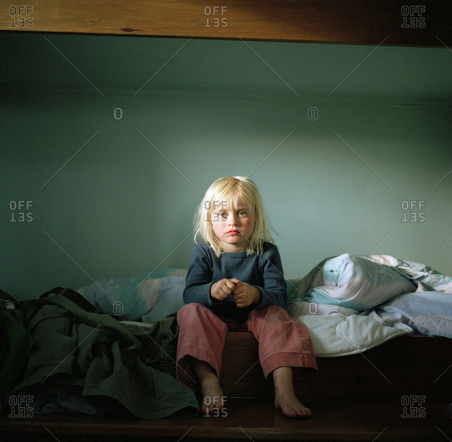 A blond girl sitting on a bottom bunk