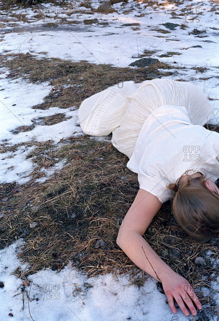 Woman lying on snowy ground