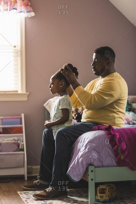 Man fixing daughter's hair in her bedroom