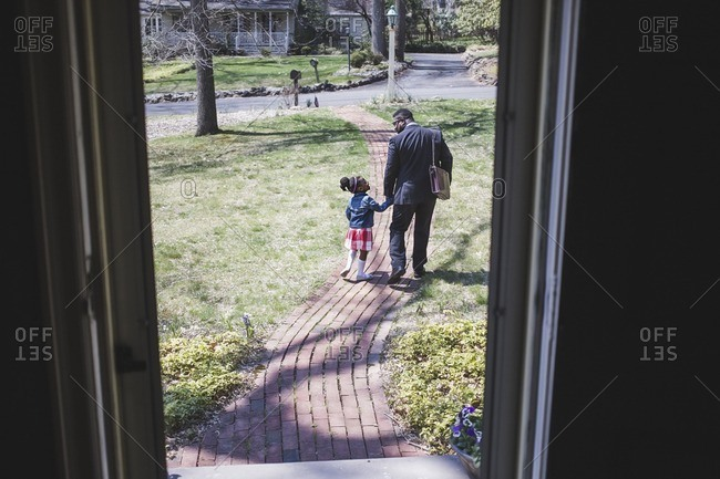 Man walking with daughter down the walkway to their house