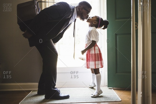 Man kissing daughter before going out the front door