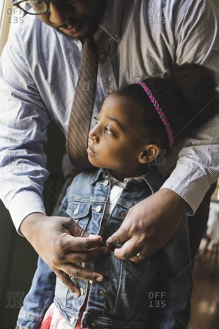 Man putting jean jacket on daughter
