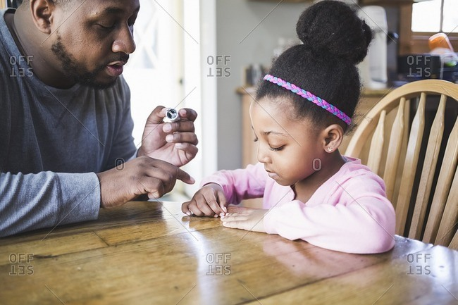 Man painting little girl's nails