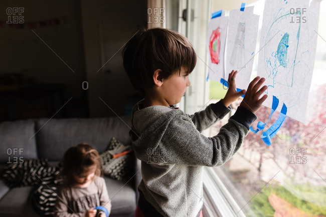 Two young children drawing on paper taped to window