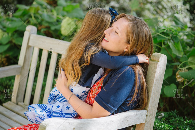 Mother and daughter hugging on a park bench