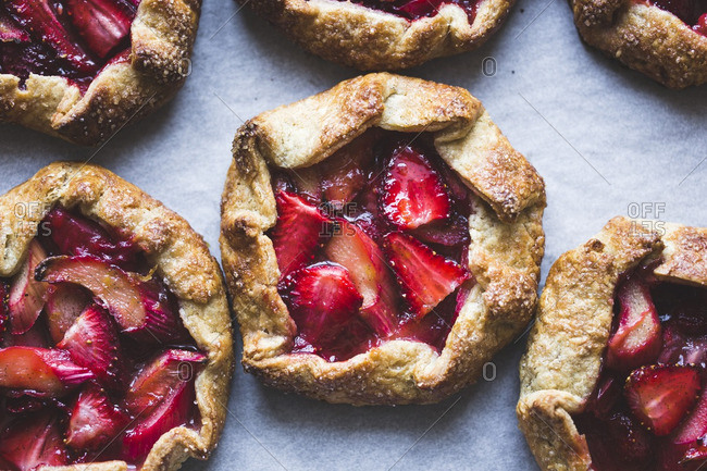 Close up of strawberry rhubarb galettes on a tray