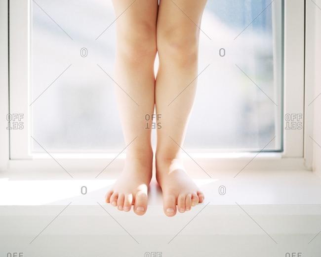 Child standing on window frame