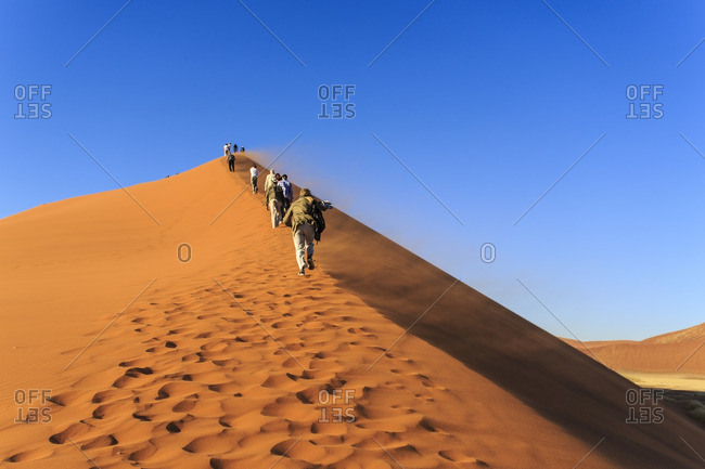 Tourists hiking up a red sand dune in Namibia