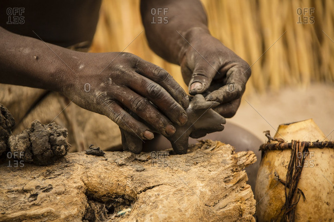 Hands of craftsperson sculpting animal from clay
