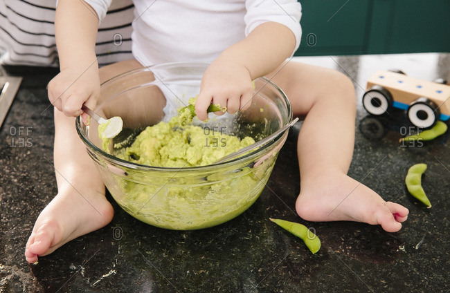 Baby with a big bowl of homemade avocado baby food