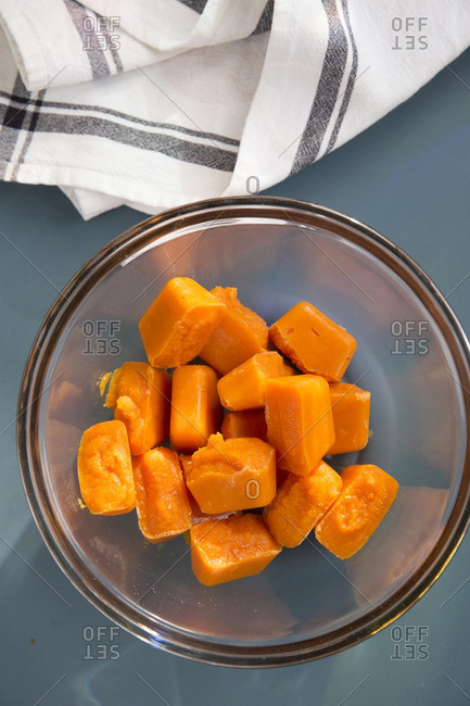 Frozen cubes of homemade baby food made from carrots in a glass bowl