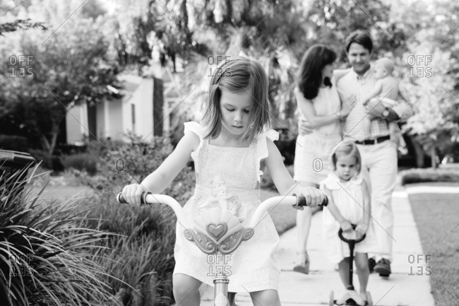 Girl riding her bike in front of her family