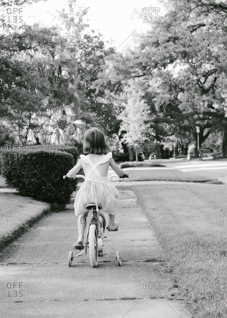 Girl riding a bike with training wheels on the sidewalk