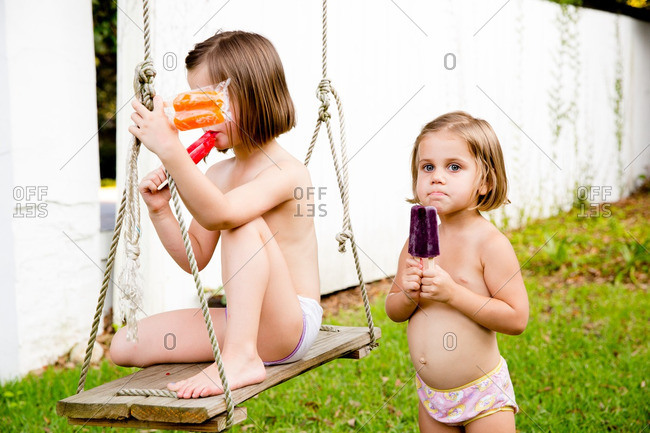 Two girls in their panties eating popsicles outside
