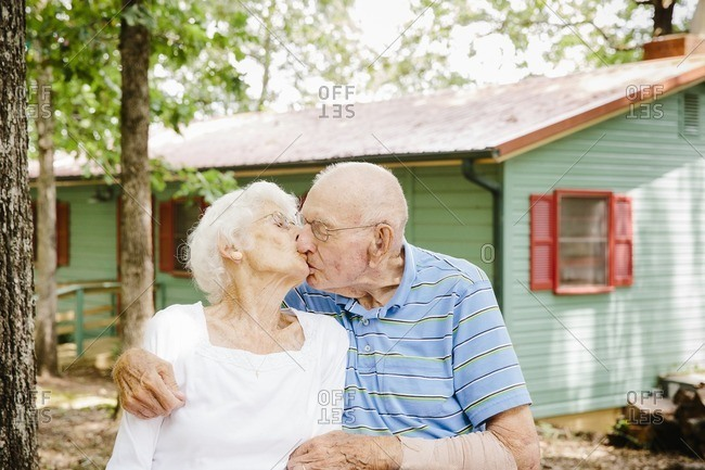Senior couple kissing outside in front of a cabin