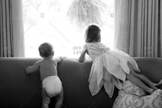 Sisters standing on the couch together and looking out the window