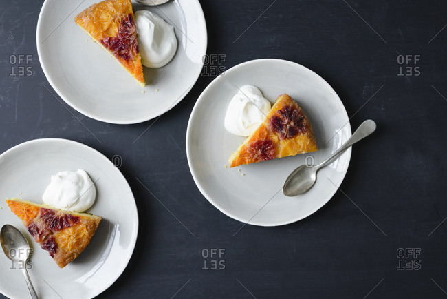 Three slices of citrus polenta upside-down cake with whipped cream