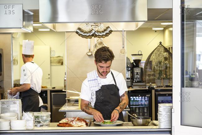 Hornbaek, Denmark - July 3, 2015: Chef plating food at Ilse Jacobsens Kurbadet restaurant