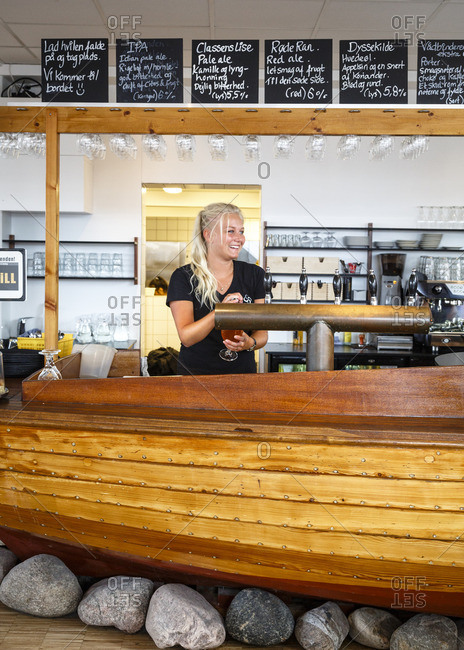 Hundested, Denmark - July 4, 2015: Female bartender pouring a beer at Halsnaes Bryghus brewery