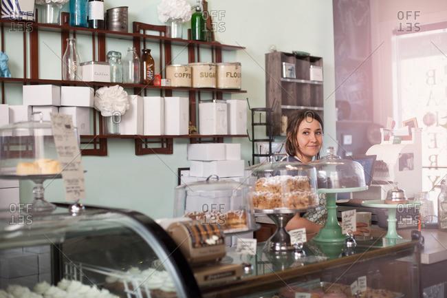Bakery owner standing behind counter of vegan, allergy-friendly bakery