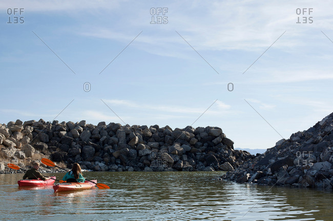 Rear view of kayakers sitting on water in kayaks facing rocks, Great Salt Lake, Utah, USA
