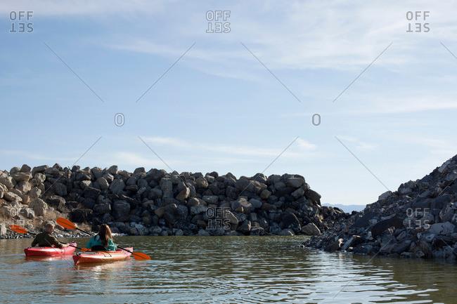 Rear view of kayakers sitting on water in kayaks facing rocks, Great Salt Lake, Utah, USA