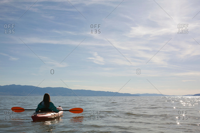 Rear view of young woman kayaker sitting in kayak on water, Great Salt Lake, Utah, USA