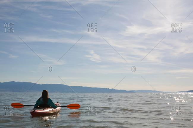 Rear view of young woman kayaker sitting in kayak on water, Great Salt Lake, Utah, USA