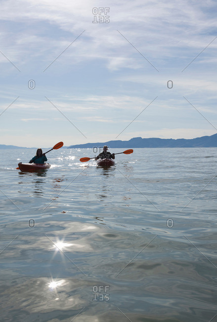 Kayakers sitting in kayaks on water in front of mountain range, Great Salt Lake, Utah, USA