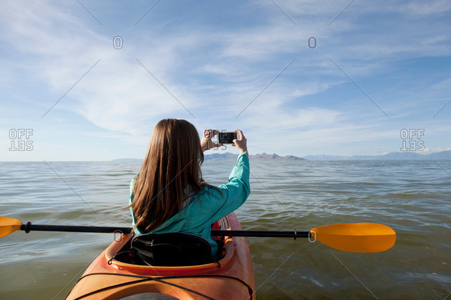 Rear view of young woman in kayak taking photograph, Great Salt Lake, Utah, USA