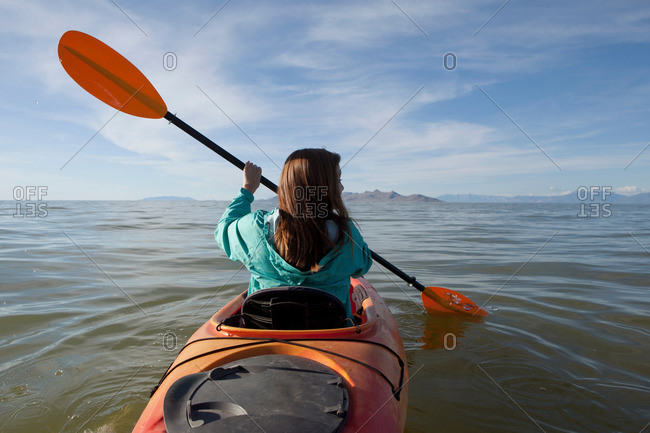 Rear view of young woman kayaking, holding paddles, Great Salt Lake, Utah, USA